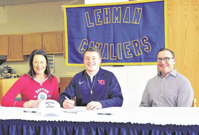 Mike Ullery/Daily Call Lehman Catholic senior Ian Smith signs his letter of intent to play football for the University of Dayton. From the left are his mother Caryn Scott, Ian Smith and father Pat Smith.