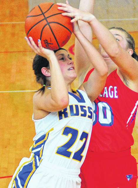 Russia's Whitney Plieman works to get off a shot against Tri-Village's Lissa Siler Saturday at Troy High School.