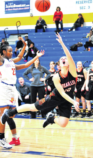 Versailles' Kami McEldowney manages to get the shot off in spite of being knocked to the floor by Purcell-Marian's Bianca Madaris Monday at Springfield High School.