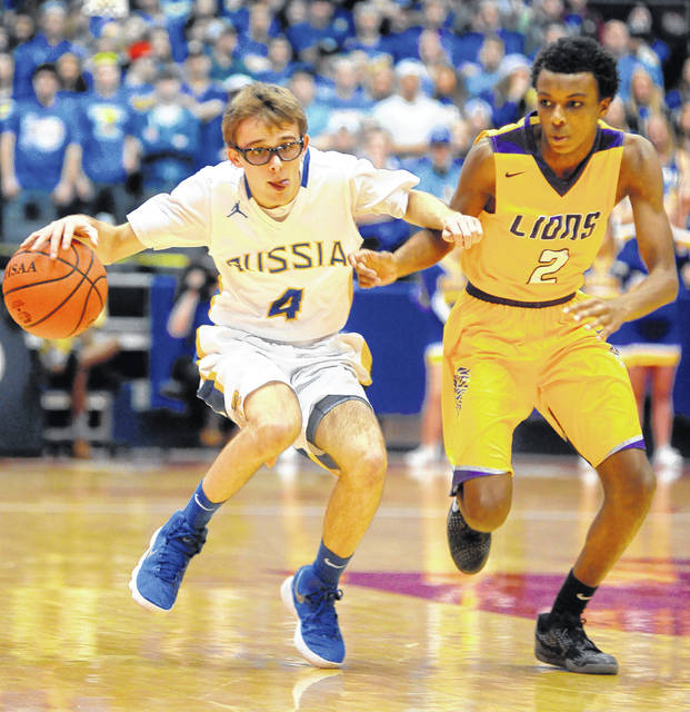 Russia's Mason Dapore drobbles past Emmanuel Christian's Jason Channels Friday night at U.D Arena in a Division IV district final.