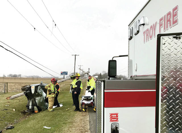 Mike Ullery | AIM Media Midwest Troy firefighters and EMS works to free the victim of a single-vehicle crash from her overturned van in the 3500 block of West State Route 41 on Monday.