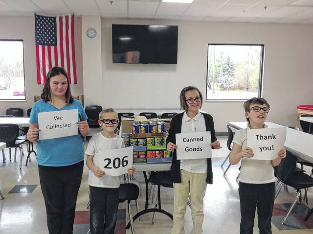 Provided photo Nicholas School students show the over 200 canned goods that the school raised in honor of the 100th day of school. Pictured are students Ciera, Ryan, Ava, and Kassidy.