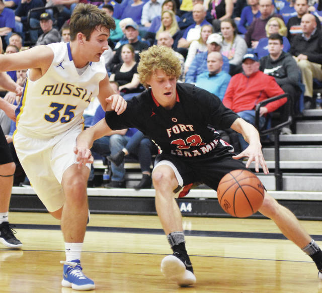 Luke Gronneberg/Aim Media Fort Loramie's Dillon Braun drives against Russia's Evan Monnier at Trent Arena Tuesday night in a Division IV regional semifinal.