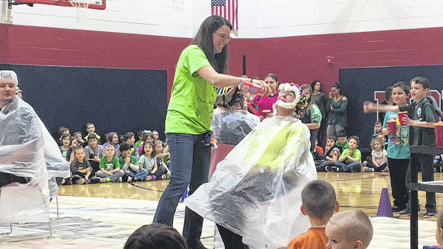 Sam Wildow | Daily Call Physical education teacher Jennifer Huelskamp (left) sprays whip cream onto teacher Jennifer Everett's (right) face for the cheddar cheese ball activity during Friday's assembly for Jump Rope for Heart at Springcreek Primary.