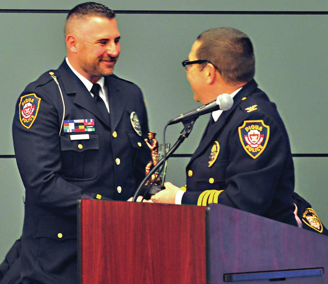 Mike Ullery | Daily Call Officer Jeremy Weber of the Piqua Police Department is awarded the 2017 Officer of the Year award by Chief Bruce Jamison during Tuesday's 4th Annual Miami County Law Enforcement Awards Ceremony at the Fort Piqua Plaza.