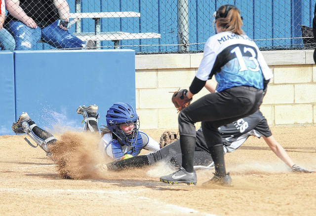 Miami East catcher Emily Adkins, attempts to put the tag on Covington baserunner Makenna Gostomski Friday at home plate as East pitcher Abigail Covault (13) backs up the play.