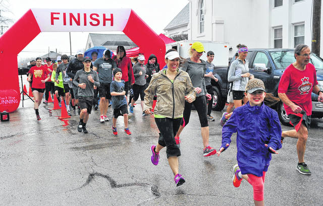 Mike Ullery | AIM Media Midwest Runners didn't let a steady rain dampen their spirits as they began the Positive + Leader + Uplifting + Supportive (PLUS) 5K Run in Covington on Saturday morning. Proceeds from the run benefit the Covington fifth and sixth grade Overnighter event.