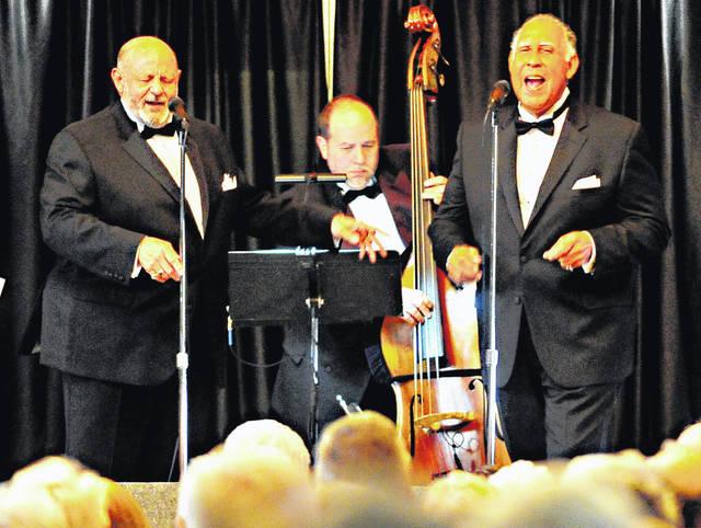 Mike Ullery | Daily Call John Mills, left, son of original Mills Brother Donald Mills, and Elmer Hopper of Platters fame perform to a sell-out crowd at the Fort Piqua Plaza Banquet Center on Thursday as part of An Evening with the Mills Brothers. The event benefits the John Johnston Farm & Indian Agency.