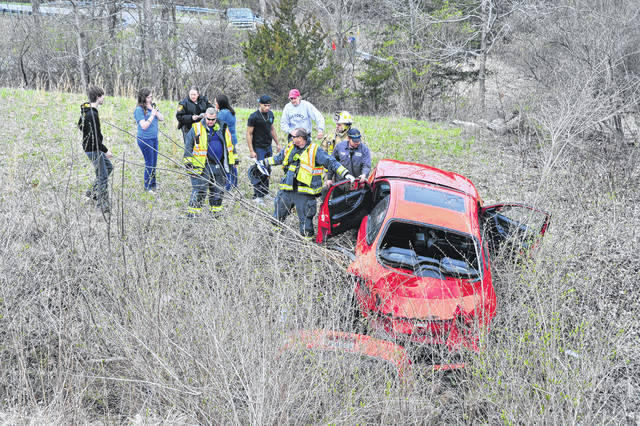 Mike Ullery | Daily Call Firefighters from Piqua and Lockington work to extricate a victim of a crash on State Route 66 north of Piqua on Saturday afternoon.