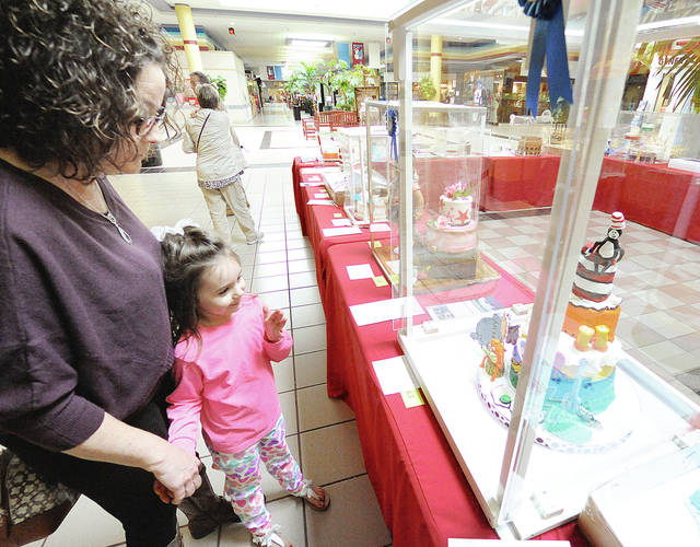"""Anthony Weber   Troy Daily News  Piqua resident Crystal Brown and her daughter, Tori, bid on several cakes during """"Cakes for a Cause"""" Friday at the Miami Valley Centre Mall Friday in Piqua. The Piqua Community Foundation held its annual event themed """"Oh! the Places You'll Go!"""" this week. Proceeds for the annual event benefits grant-funding for The Piqua Community Foundation."""