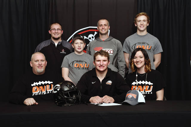 Ben Robinson/GoBuccs.com Joey Schmelzer (front center) commits to continue his education and football career at Ohio Northern University with his parents Chad (front left) and Jannette (front right), along with (left to right) head coach Tyler Cates, his youngest brother Trey, assistant coach Jason Sutherland and brother Cade Schmelzer looking on.