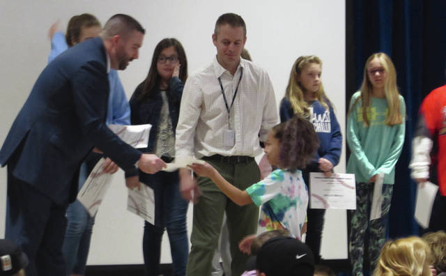 Sam Wildow | Daily Call Piqua Central Intermediate School (PCIS) student Jada Covault accepts a certificate from PCIS Principal Josh Kauffman during the Breakfast of Champions held Monday evening.