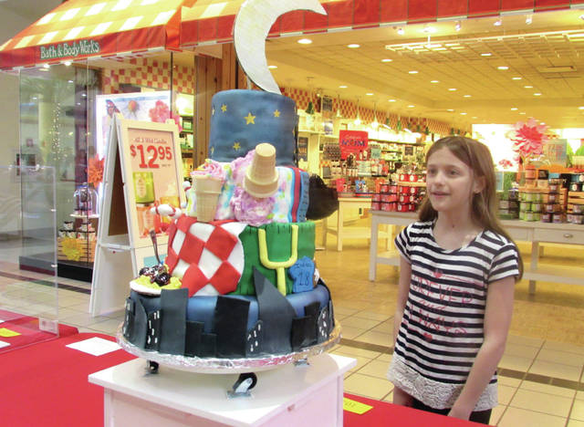 "Cody Willoughby | AIM Media Midwest Morgan Brunson, 11, of Troy, admires one of the VIP cakes on display during the 13th annual ""Cakes for a Cause"" event on Thursday at Miami Valley Centre Mall in Piqua. VIP cakes were based upon their incentive sizes, and included contributions from Unity National Bank, Miami Valley Steel Services, Jamieson & Yannucci Funeral Home, and Stacy and Benny Scott."