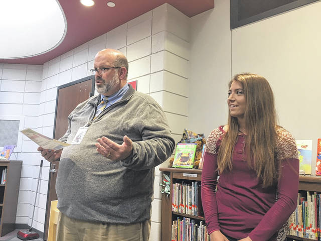 Sam Wildow | AIM Media Midwest Covington High School Principal Jon Geuy (left) honors high school senior Shae Robinson during the Covington Board of Education's student spotlight on Wednesday evening.