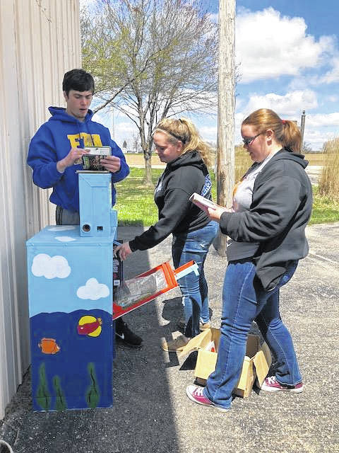 From left, Miami East FFA members Alex Isbrandt, Kylie Blair and Emily Thimmes fill the Little Free Library box at the Staunton Township building last week. The FFA chapter installed seven book boxes throughout the Miami East school district last week.