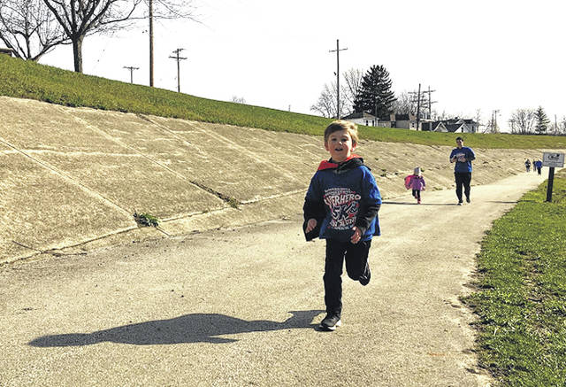 Cody Willoughby | AIM Media Midwest Charlie Zimmerman, 5, of Piqua displays his super-speed, with father Brad Zimmerman and sister Amelia, 3, bringing up the trail during the Superhero Fun Run 5K race on Saturday at Lock 9 Park in Piqua.