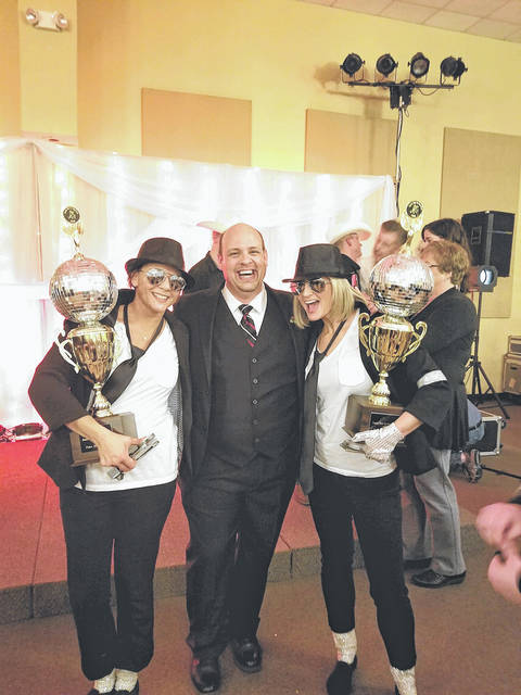 Provided photo Jordan Knepper, executive director of the Piqua Arts Council, is flanked by Kelly Meckstroth, left, and Kristen Mikolajewski, winners of the Most Entertaining and Mirror Ball trophies at this year's Dancing with the Piqua Stars.