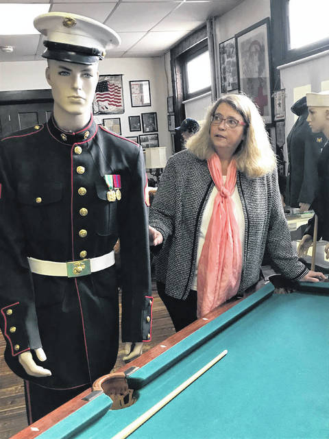 Melody Vallieu | AIM Media Midwest Karen Purke stands with a mannequin wearing a Marine's uniform from the 1990s.