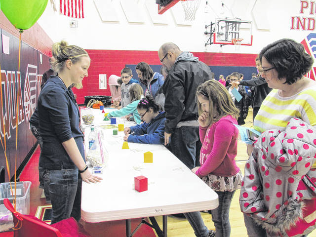 Sam Wildow | Daily Call Brittany Price, far right, watches as her daughter, Lily Willcox, center right, constructs a shape using 15 toothpicks and 15 small marshmallows at Piqua Central Intermediate School's Math Night on Thursday evening.