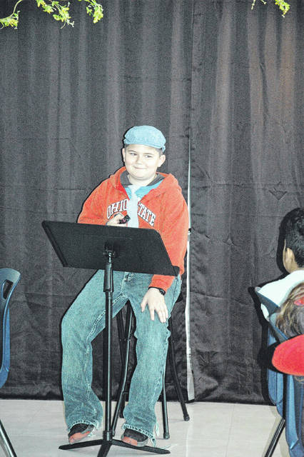 Cody Willoughby | AIM Media Midwest Usher Tyler Scherer takes his turn to present a poem during the Poetry Cafe held at Piqua Central Intermediate School on Monday.