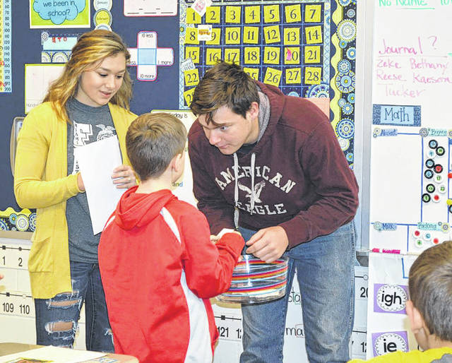 Provided photo FFA member Kelsea Drake, left, and Ethin Bendickson work with a student in Jennifer McCuistion's first grade class in a game of animal charades. Students were asked to act out an animal and their classmates could name the animal then say if it was a domestic or wild animal.
