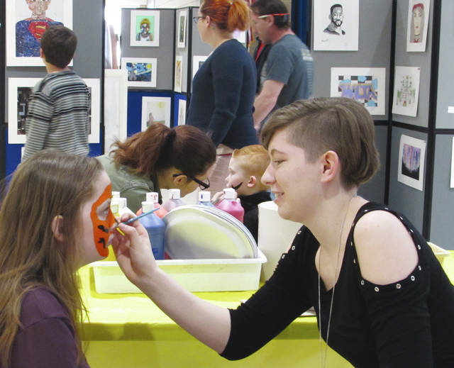 Sam Wildow | Daily Call Piqua High School student Laya Barker (right) paints Piqua Central Intermediate School student Gracee Bruno's face at the district-wide art show held Saturday afternoon at PCIS.