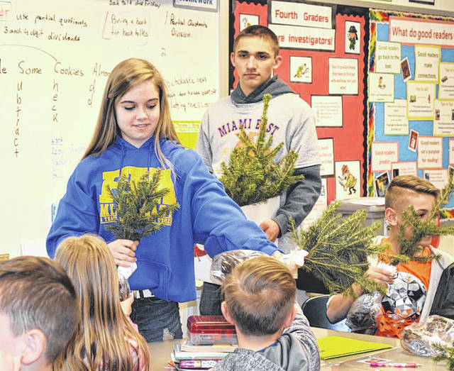 Provided photo Members of the Miami East-MVCTC FFA's Environmental Committee distributed trees to all Miami East Elementary fourth graders. Committee members shown are Megan Honeyman and Luke Gilliland.