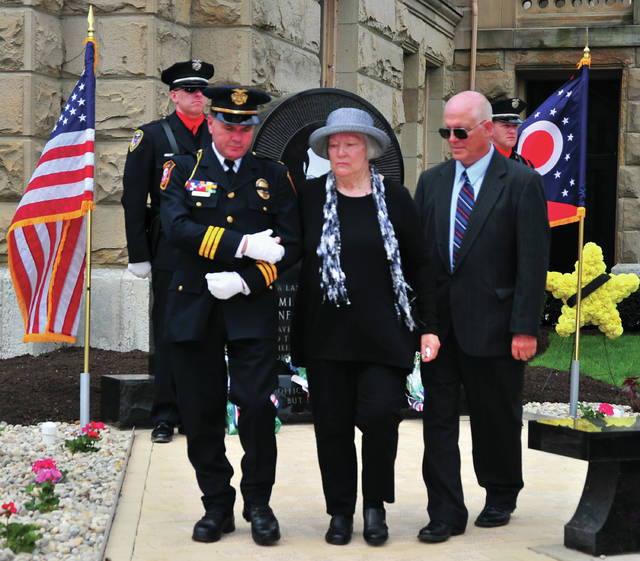 Mike Ullery | Daily Call Piqua Deputy Police Chief Marty Grove escorts Nancy Mulder, widow of fallen Piqua Police Officer Jan Mulder, during Wednesday's Miami County Law Enforcement Memorial Service at the Miami County Courthouse Plaza in Troy. Jan Mulder was killed in the line of duty in 1970.