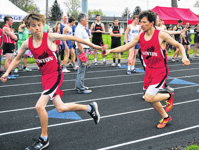 Newton's Owen Via, right, hands off the baton to Tristin Benedict in the boys 4x800 meter relay event at the Covington Invitational Track Meet on Friday.