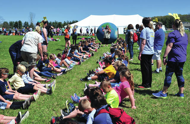 Piqua Catholic first and second grade students learn about the movement of planet Earth by using an Earth Ball during day one of the Miami County Park District's Hug the Earth Festival at Stillwater Prairie on Tuesday.