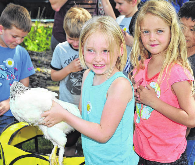 Baylee Bigelow is excited to get to hold a chicken as classmate Mia Byrer waits her turn during Miami East Ag Day at the Miami County Fairgrounds on Friday. The girls are kindergarteners at Concord Elementary School in Troy.