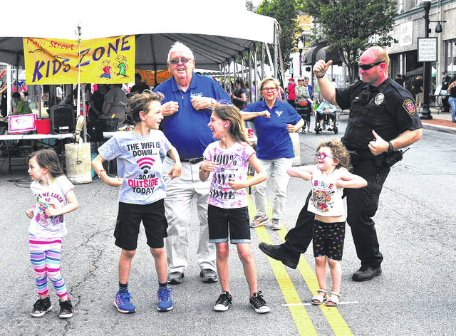 Mike Ullery | Daily Call Duane Bachman, Melinda Sillman, and Officer Brett Marrs of the Piqua Police Department join children in the Chicken Dance during Friday's annual Taste of the Arts event in downtown Piqua.