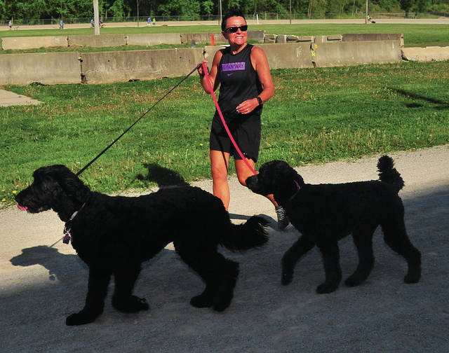 Mike Ullery | Daily Call Tammy Pence and her two canine companions run Saturday's 5K-9 event at the Miami County Fairgrounds. The event, hosted by Miami East and Milton-Union FFA is a fundraiser for the Miami County Animal Shelter. Saturday's event saw 83 runners raise more than $500 for the shelter.
