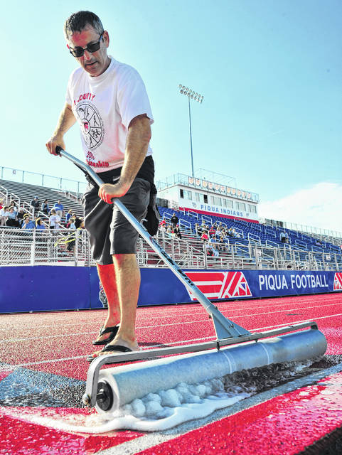 Mike Ullery | Daily Call Piqua coach Scott Kaye uses a squeegee to clear water from the track at Alexander Stadium/Purk Field on Tuesday following a heavy rain that delayed the start of the Division III District Track. The meet got underway after about an hour's delay. District track competition in all three divisions will continue through Satuday.