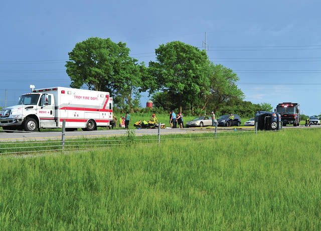 Mike Ullery | Daily Call Troy firefighters and medics, along with troopers from the Piqua Post of the Ohio State Highway Patrol work the scene of a roll-over crash on northbound I-75 at the 78 mile marker on Sunday evening.