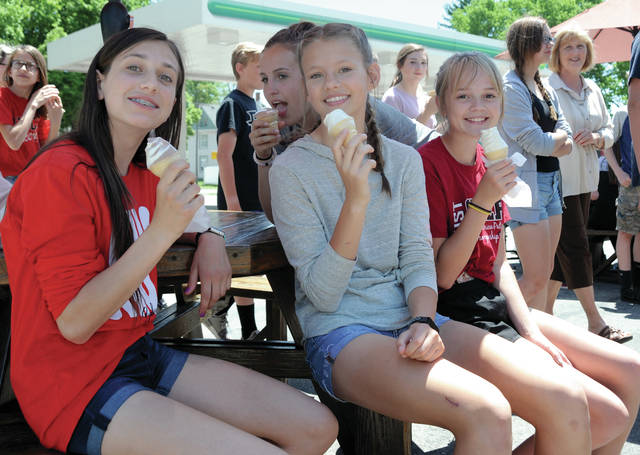 Mike Ullery | Daily Call Covington Junior High students Taylor Roth, Ella Renley, and Erika Gostomsky, seated l-r, and Reaghan Lemp, center rear, enjoy ice cream cones from Sweet Treats in Covington on Wednesday afternoon. Students were treated to the end of the year field trip by school staff members.