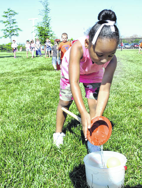 Mike Ullery | Daily Calll Kindergarten student A'Leonna Taborn pours water into a bucket from a plunger during Field Day at Springcreek Primary School on Friday.