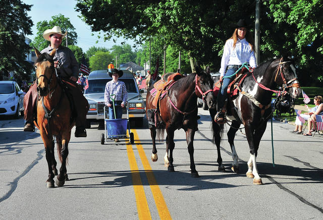 Mike Ullery | Daily Call A riderless horse, boots reversed in the stirrups, a traditional memorial to honor fallen Cavalry soldiers, is led along the Memorial Day Parade route in Piqua on Monday.
