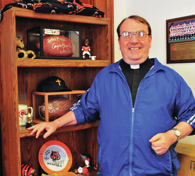 Mike Ullery | Daily Call Father Tom Bolte poses with some of his sports memorabilia in his parish office this week.