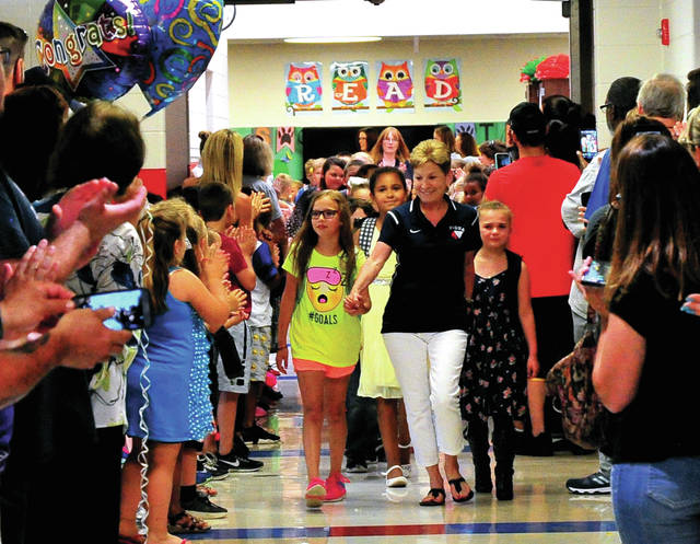 "Mike Ullery | Daily Call Parents, students and staff line the halls to ""Clap Out"" Washington Primary School teacher Linda DeWeese and third-grade students as they march down the hallway at the school one last time on Thursday afternoon. The students will be moving up to Piqua Central Intermediate School in the fall and DeWeese is retiring following 22 years of service to the students at Piqua City Schools."