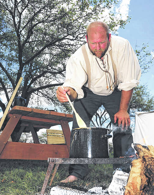 Mike Ullery | Daily Call Wesley Burnside of Ft. Loramie tends to cooking at the primitive encampment during last year's History Alive at the John Johnston Farm and Indian Agency.