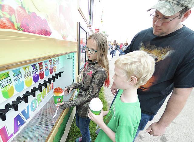 Anthony Weber | Troy Daily News  David Carr along with his children Chastity and David, of Dayton, get a shaved treat at Kona Ice recently during the 2016 Gourmet Food Truck Competition and Rally in Troy.