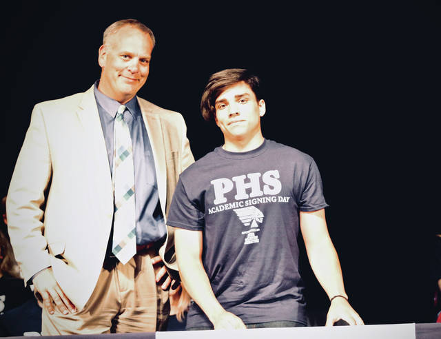 Piqua High School senior Jan Adorno-Soto signs his Academic Letter of Intent with principal Rob Messick during Monday's annual Academic Signing Day. Adorno is planning on attending Urbana University in the fall. A total of 45 Piqua seniors signed letters of intent to continue their education next year.