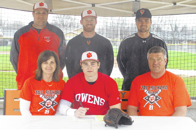 Kyle Shaner/Aim Media Photo Versailles senior Noah Richard committed to the Owens Community College baseball team on Saturday.In fron wiht Richard are his parents Peggi Richard and Mark Richard,. In back (left to right) are Versailles assistant baseball coach Brad Koopman, Versailles baseball coach Ryan Schlater and Versailles Athletic Director Doug Giere.
