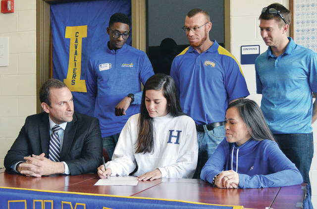 Luke Gronneberg/Aim Media Photo Lehman's Catholic senior Alanna O'Leary, center, front, signs her letter of intent to compete in track for Hillsdale College at Lehman recently. Sitting next to her are are her dad, Rob O'Leary, left, and mom, Rose O'Leary. Lehman coaches standing are, left to right, assistant track coach Denzell Boham, head track coach Dwane Rowley, and head cross country coach Kyle Hermiller.