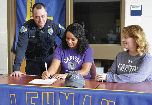 Luke Gonneberg/Aim Media Photo Lehman Catholic senior Camille Brown, center, signs her intent to play soccer for Capital University as her coach Jeremy Lorenzo, left, and her mom Kim Brown, look on at Lehman recently.
