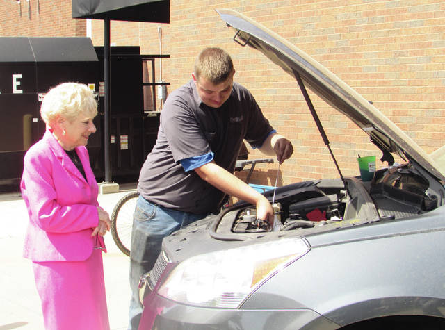 Sam Wildow | AIM Media Midwest Upper Valley Career Center Superintendent Dr. Nancy Luce, left, watches as student Bryce Kohler demonstrates how to check a vehicle's oil during the Miami County Safe Communities' kick-off event for the Click It or Ticket campaign on Tuesday.