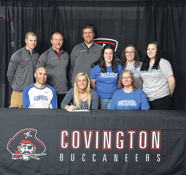 Ben Robinson/GoBuccs.com Jordan Crowell (front-center) signs her letter of intent to play college basketball at Bethel College in Indiana. In front with Crowell are Bethel College coach Eric Gingerich and her mother Kim Crowell. Standing (left to right): Covington assistant coach Brandon Studebaker, Covington coach Jim Meyer, Covington assistant coach Adam Sweigart and Jordan's sisters Jamie, Jessie and Josie Crowell.