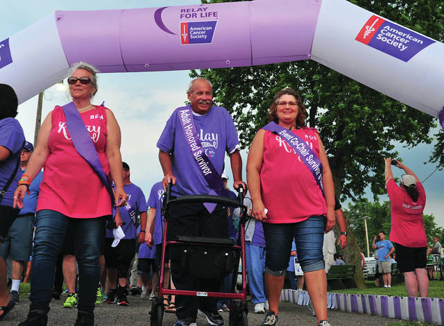 Mike Ullery | Daily Call Miami County Relay For Life co-chairs Belinda Anderson, left, and Robin Hetzler, right, walks the Survivors' Lap with Tom Goffena of Sidney to kick off the 2018 Miami County Relay For Life event at the Miami County Fairgrounds.