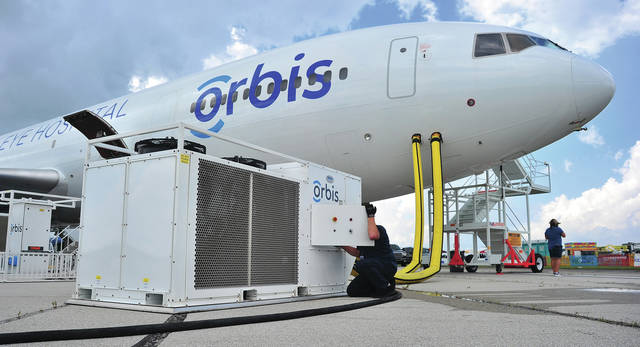 Mike Ullery | AIM Media Midwest An Orbis crew membe checks out one of the portable generators that power the DC-10 Flying Eye Hospital when on the ground, at the Vectren Dayton Air Show this week.